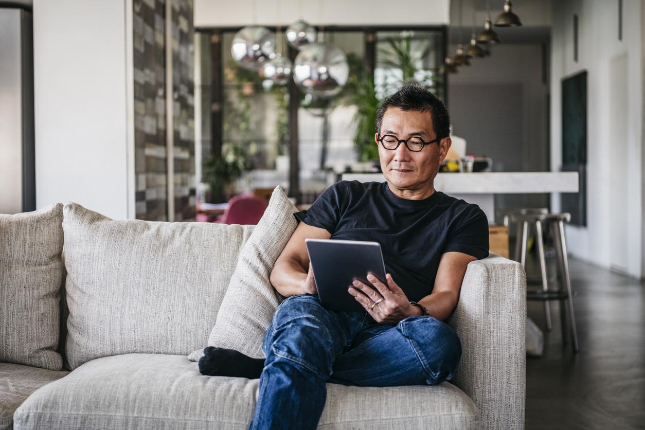 Mature man wearing glasses using digital tablet