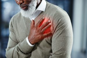 Older man clutching his heart in discomfort