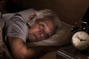 Older man struggling to fall or stay asleep