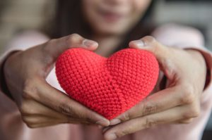 Adult woman presents knitted heart