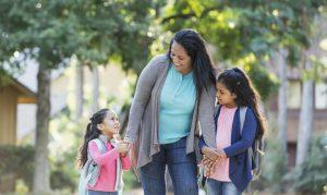 Hispanic mother taking her two girls to school