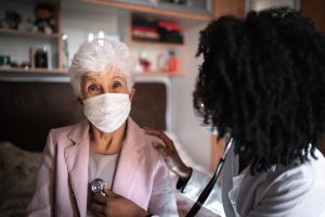 Portrait of patient - senior woman and health visitor during a home visit