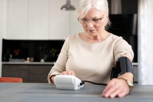 Older woman recording her blood pressure