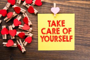 Take Care Of Yourself Written on a yellow sticky note with red hearts