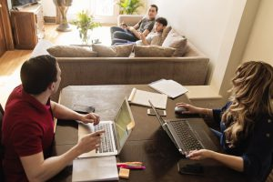 Group of young adults spend time together in living room on computers