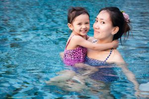 Girl playing with her mother in pool