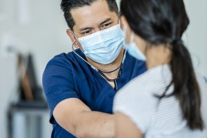 Clinician with mask examines female pediatric patient