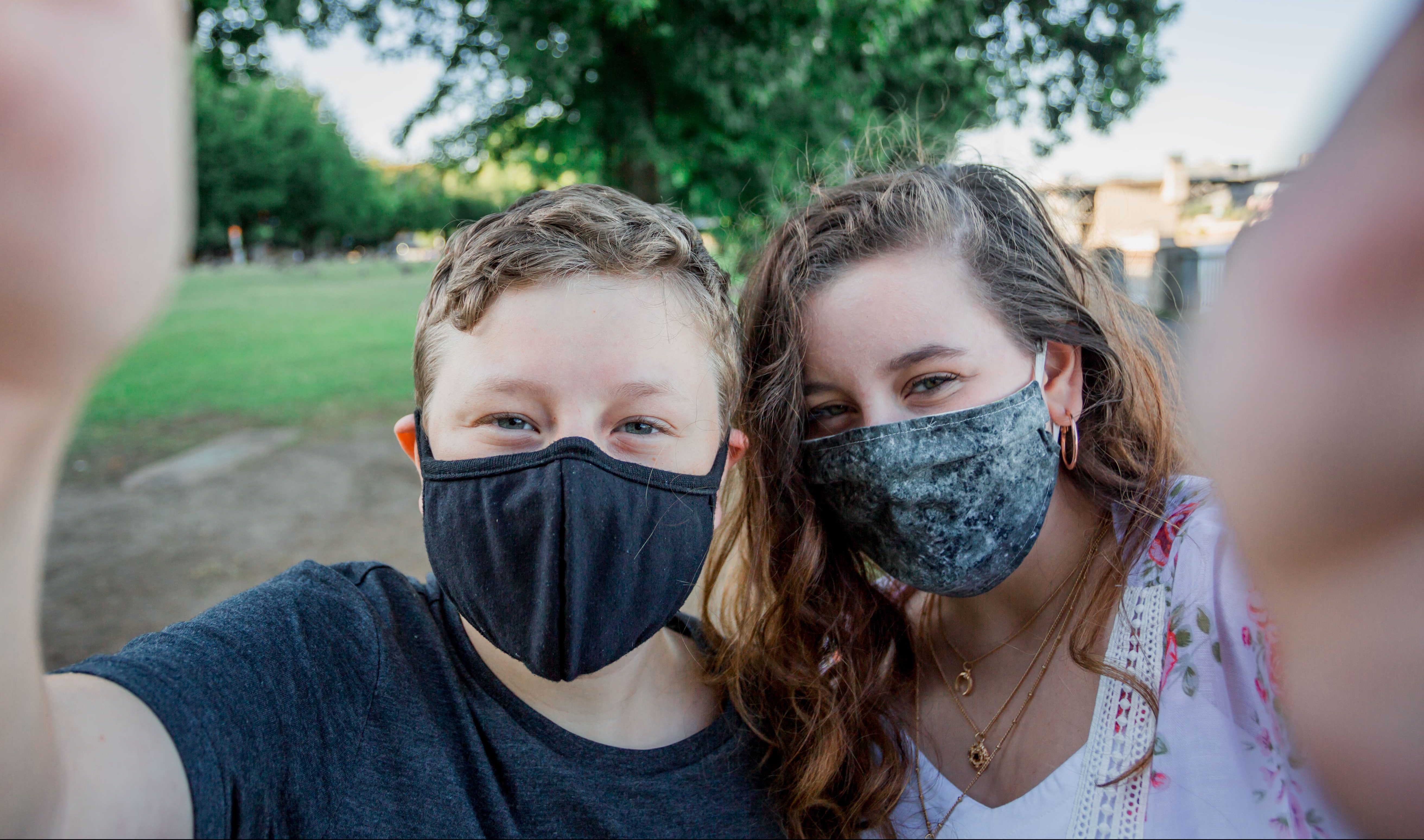 Two children happily wearing masks