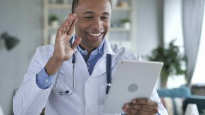 A doctor using a tablet and waving at his patients during a virtual care session