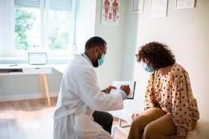 African American male doctor with surgical mask goes over paperwork in exam room with female Latina patient wearing surgical mask