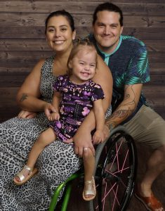 Woman in wheelchair with daughter and hu