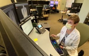 Doctor looking at telehealth screens