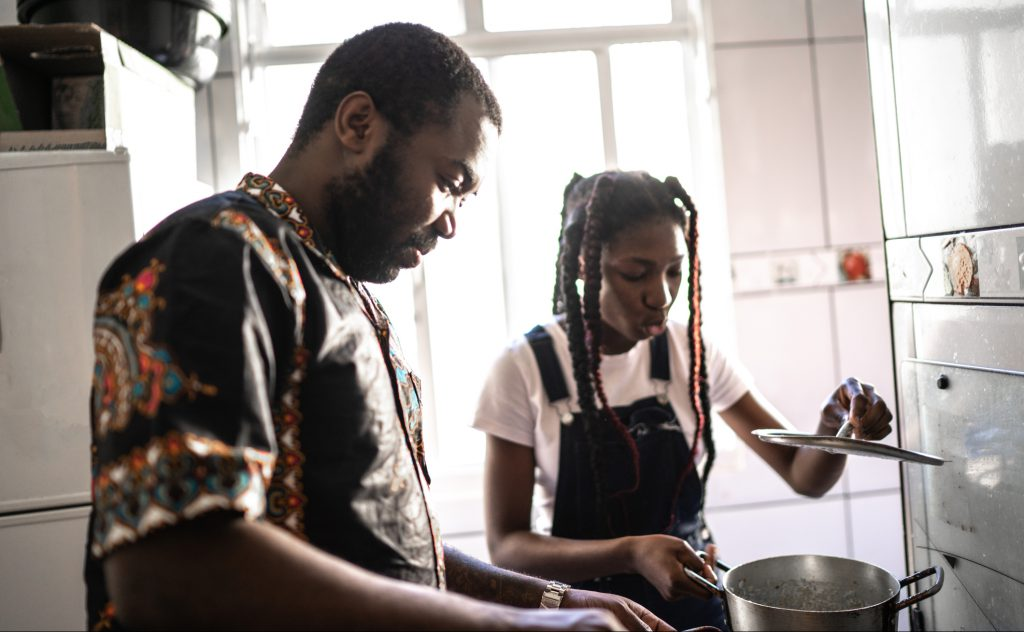 African American dad and daughter cooking over a stove at home