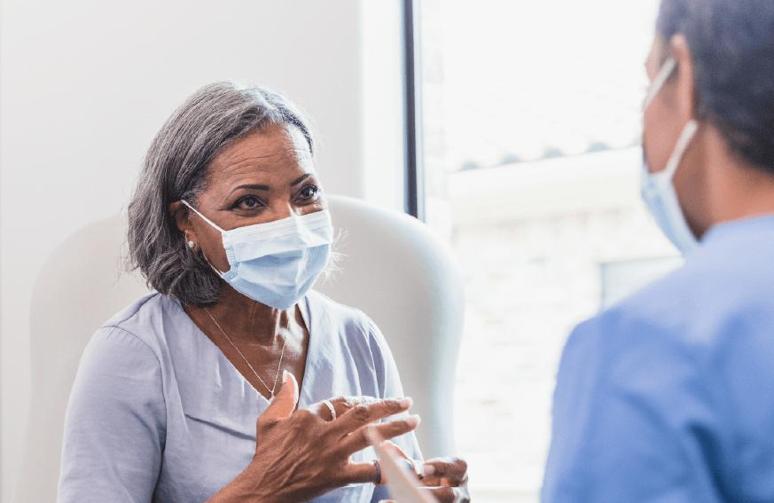 Elder woman wearing a mask speaks with her doctor.