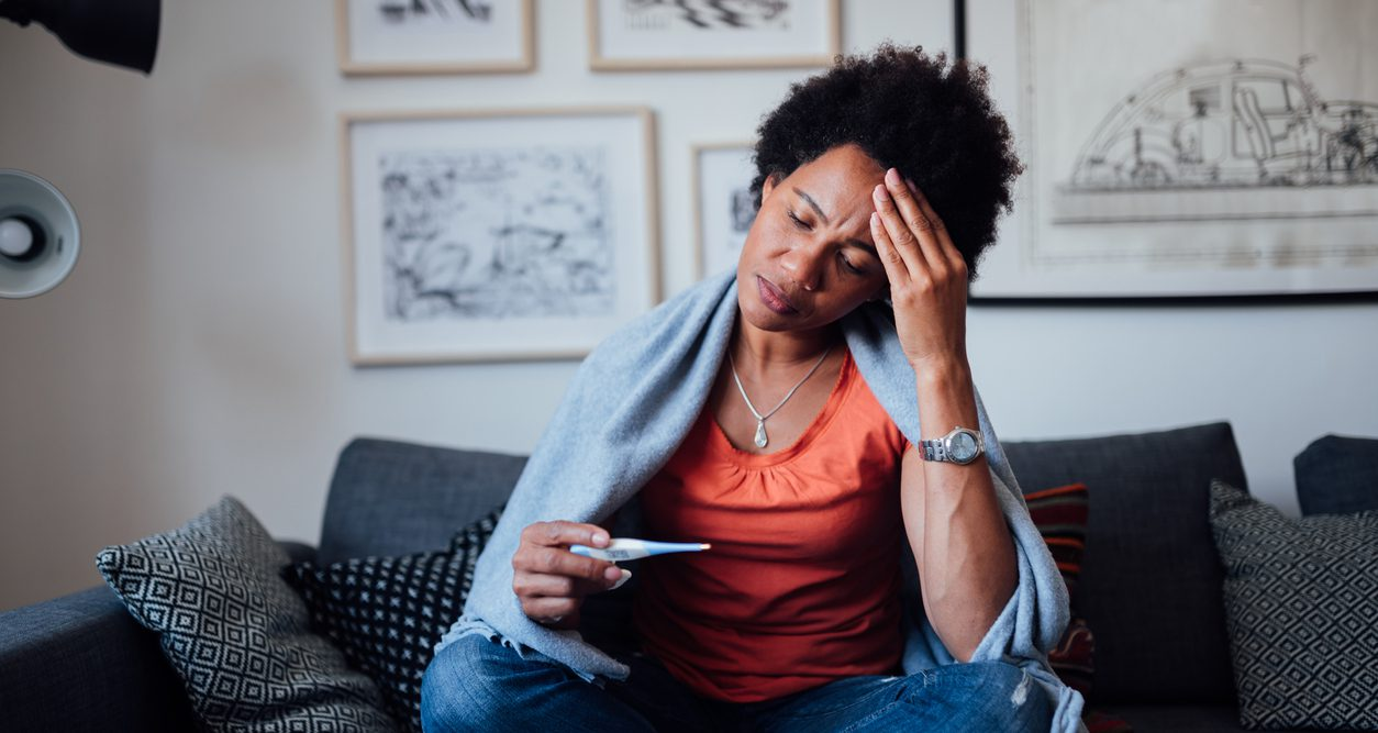Worried Black woman sitting on a couch, feeling symptoms.
