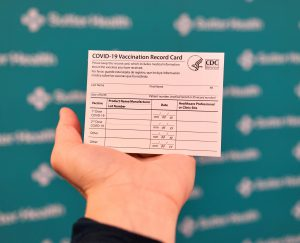 Hand holding blank COVID-19 vaccination card