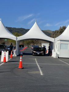 Cars in white tents at county fairgrounds vaccination site