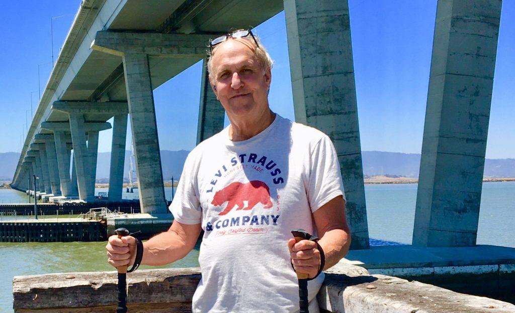 Man on bridge with walking sticks
