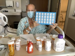 Man with medications and pill case