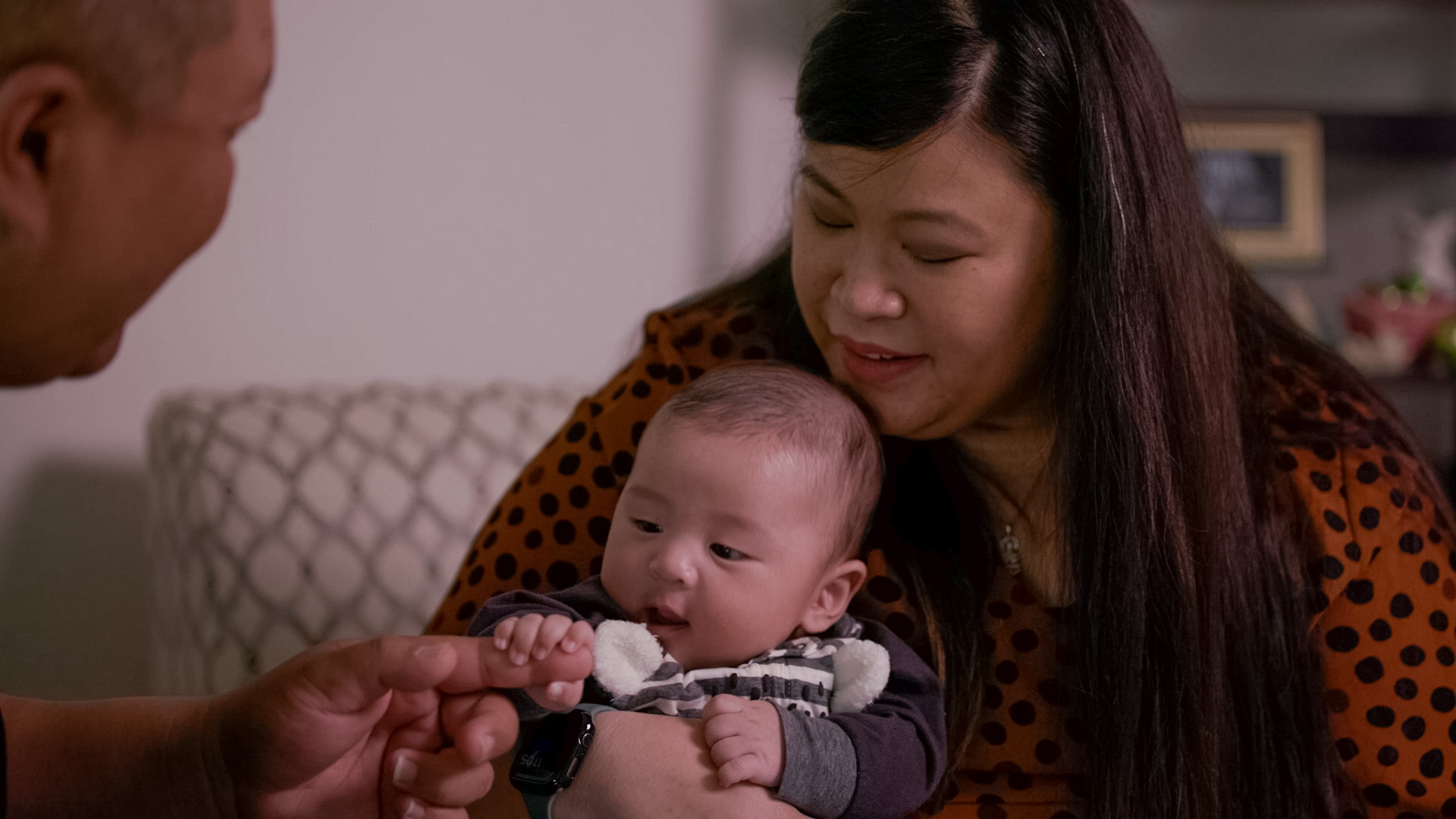 Asian couple sit on couch while doting on their baby boy