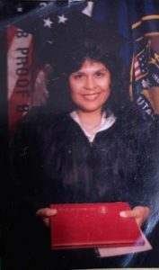 Latina woman in graduation cap and gown holding her diploma