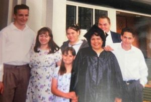 Latina woman in graduation cap and gown poses with her family