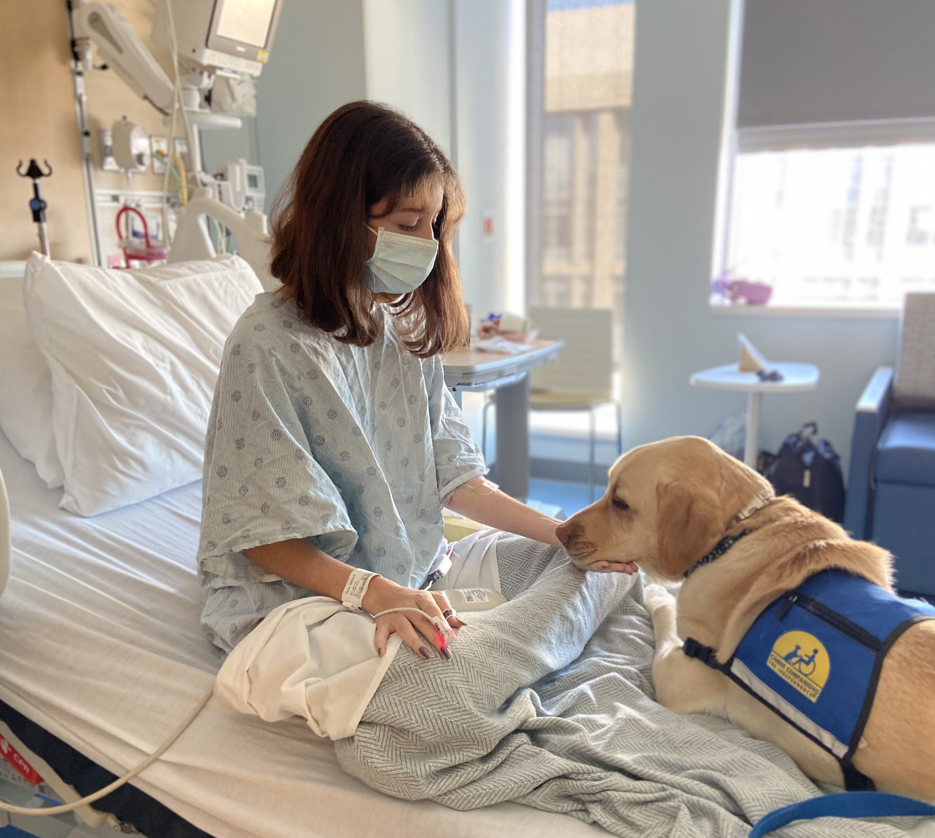 Young teenage girl is comforted by creme-colored Omega, CPMC's certified facility dog from Canine Companions