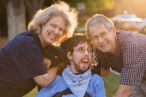 Parents pose with their son who is in a wheelchair on a sidewalk with the sun glowing behind them
