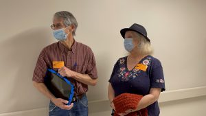 Husband and wife wearing surgical masks look down a hospital hallway