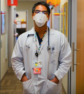 Dr. Brian Prystwosky stands in his office hallway in his white doctor's coat