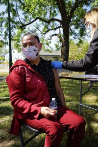 A Latina woman sits down to receive her COVID-19 vaccine at a community pop up clinic in Santa Rosa, Calif.