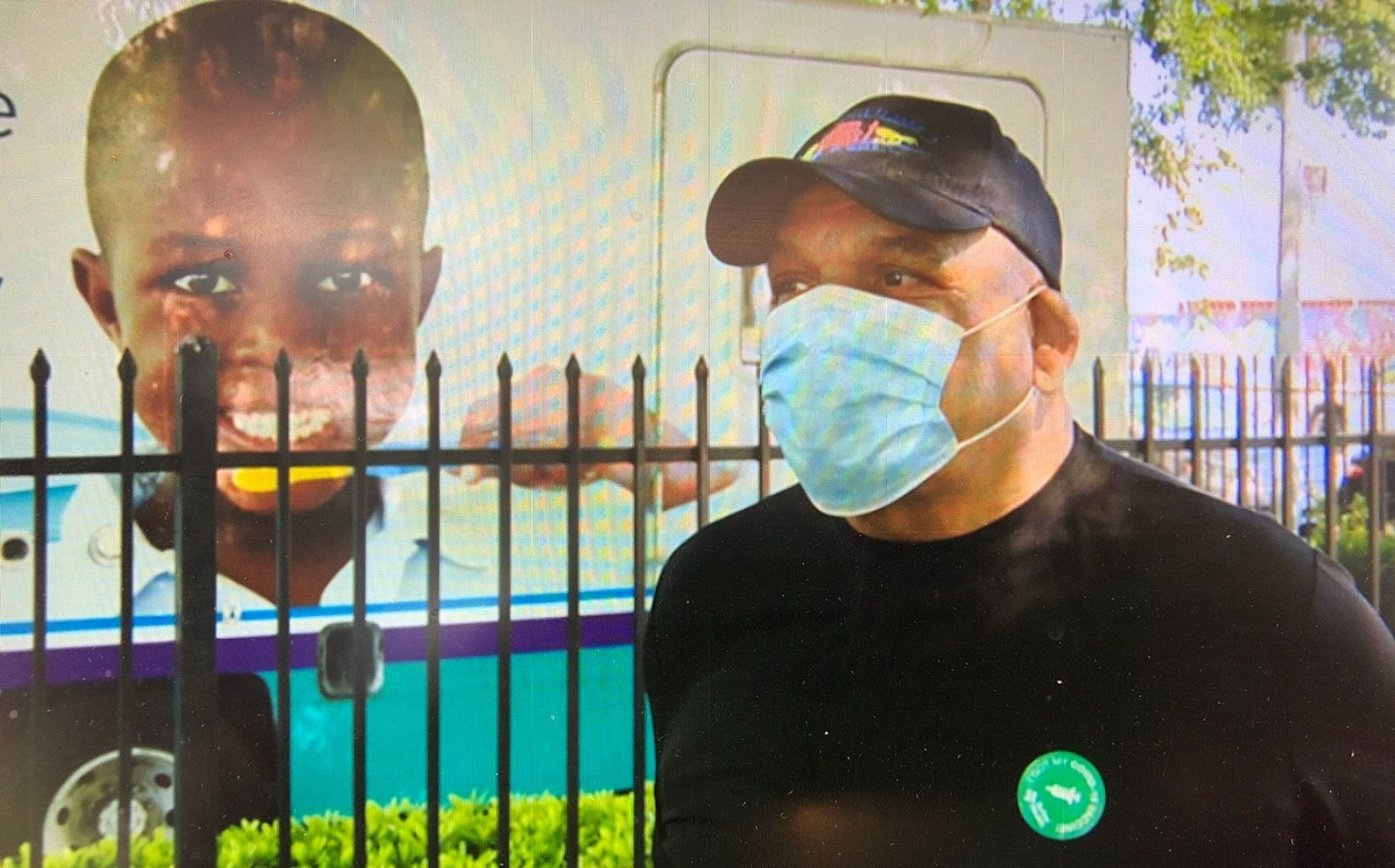 African American male with surgical mask stands alongside black iron fence and mobile healthcare van with African American boy's image