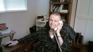 man with buzz cut sitting at desk talking on the phone