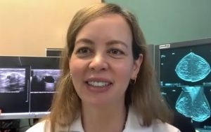 Radiologist with breast scans behind her