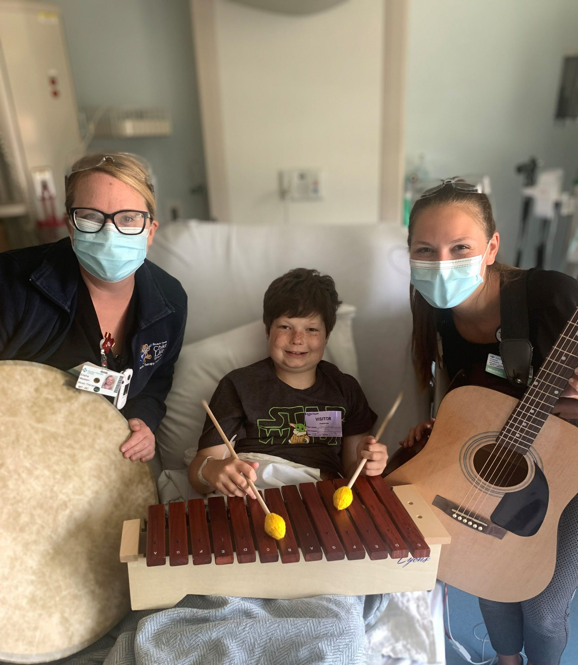 CPMC's music therapists post with Dylan Leeder, a cancer patient receiving treatment and who was helped by music therapy