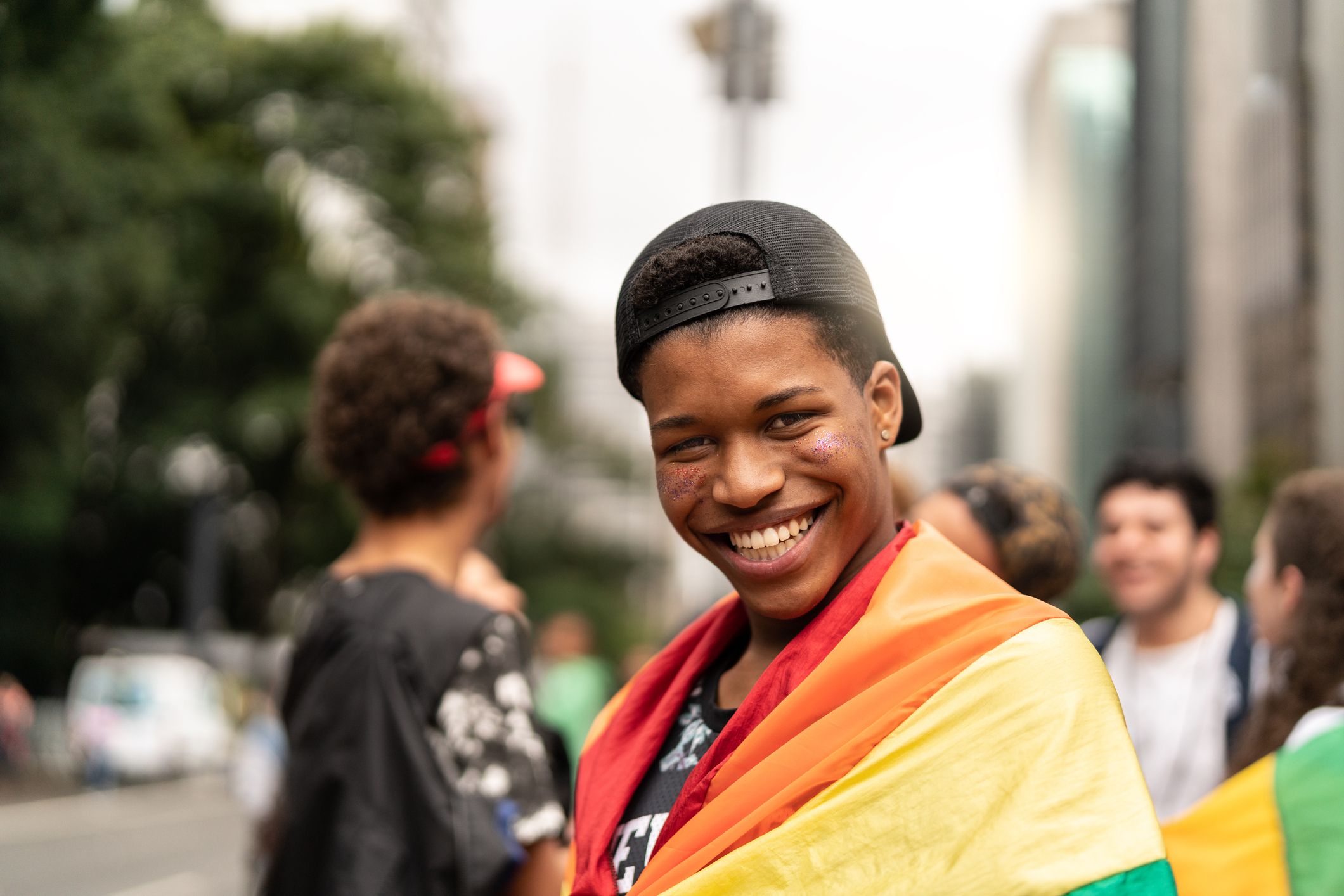 Portrait of young man with rainbow flag with friends on background at Gay Parade stock photo