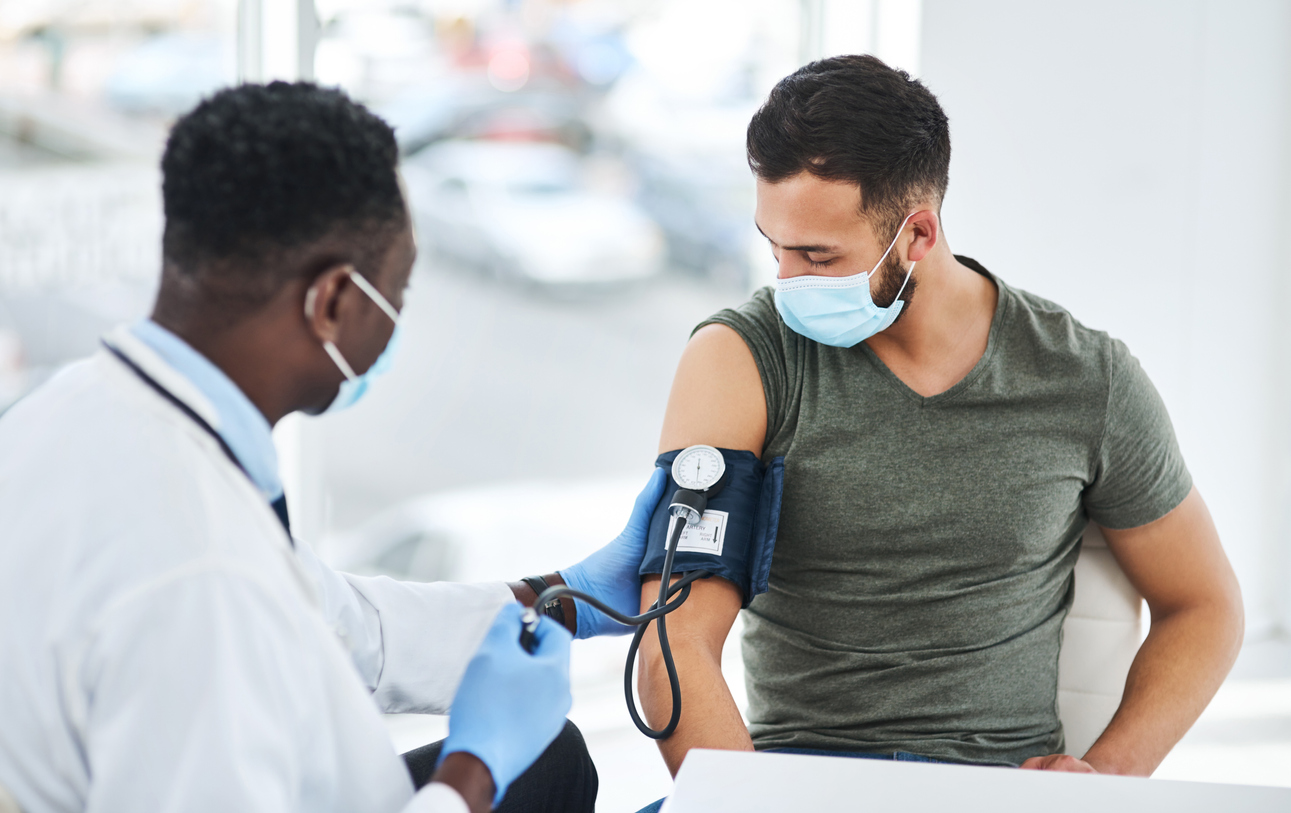 Man having blood pressure checked by Black doctor