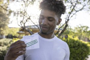 Young Black man holding COVID vaccination card