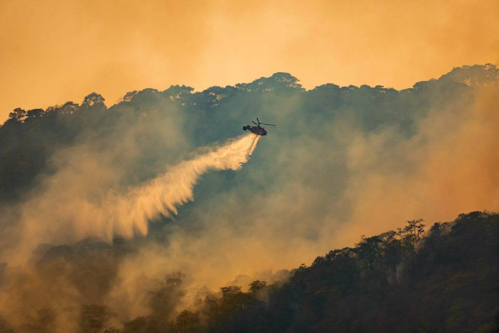 Helicopter drops water on a smoky blaze