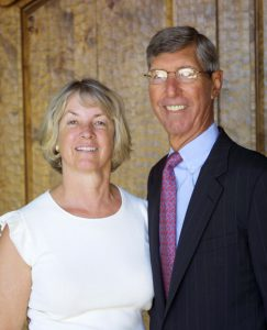 Blonde woman in white blouse and gray-haired man with glasses in suit pose for portrait