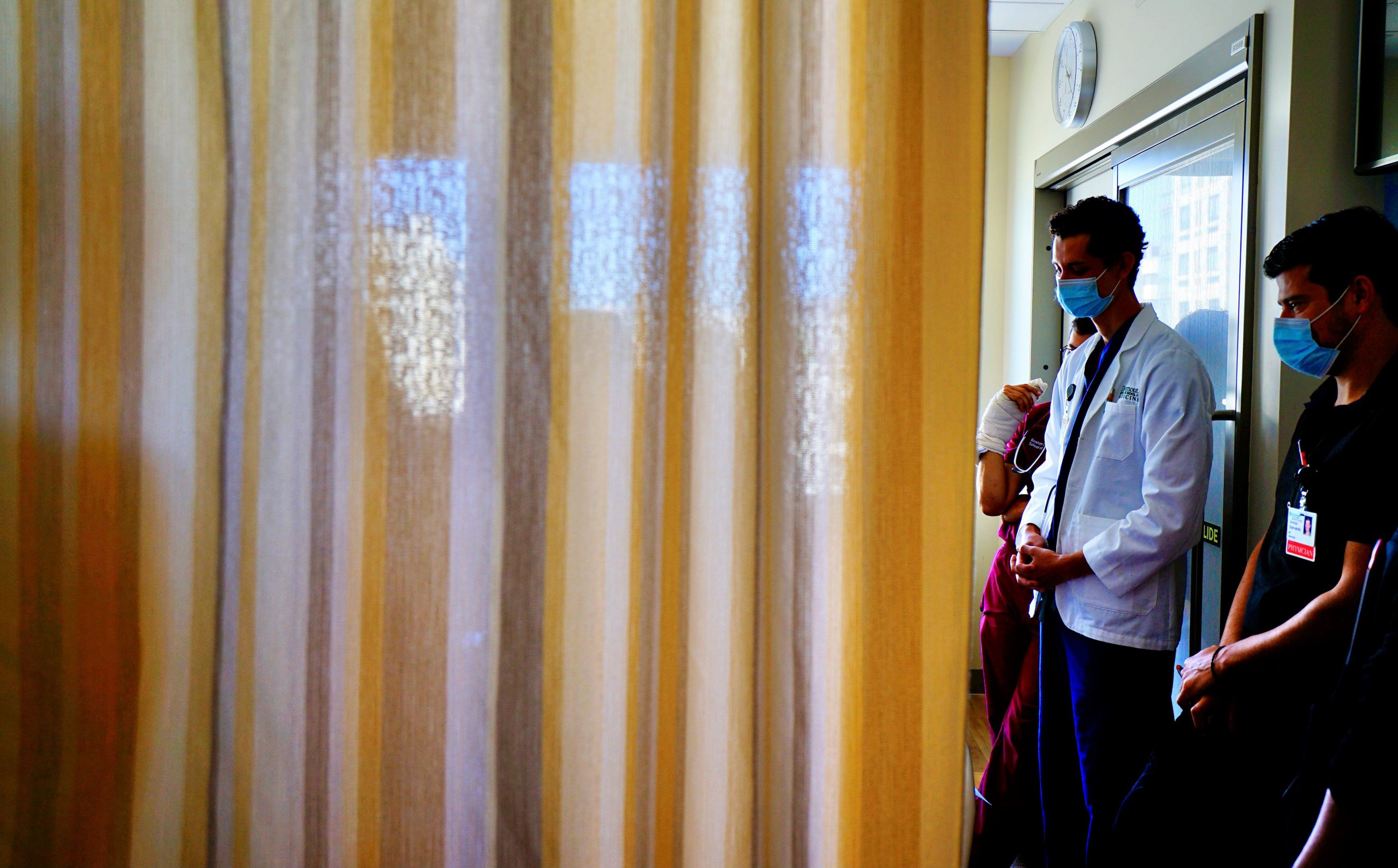 Residents greet a patient behind their bed curtain