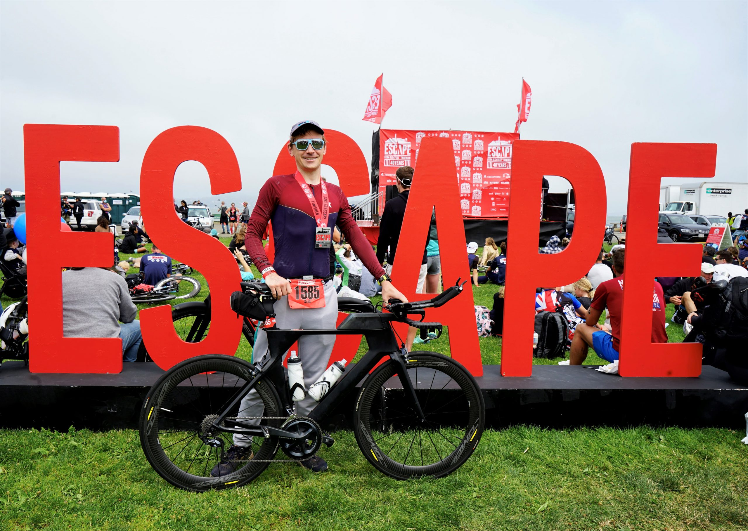 Scott Grubb stands behind a giant escape sign with his racing bike after competing in the Escape from Alcatraz Triathlon in San Francisco in August 2021