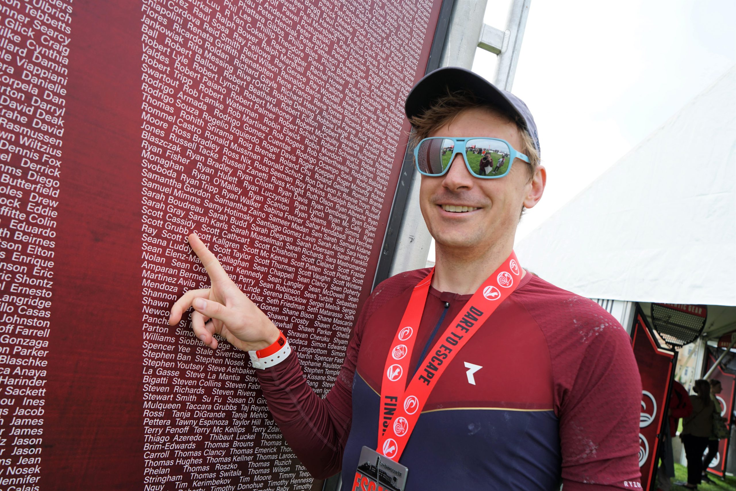 Scott Grubb points to his name as one of the 2,000 participants in the Escape from Alcatraz Triathlon in San Francisco, CA
