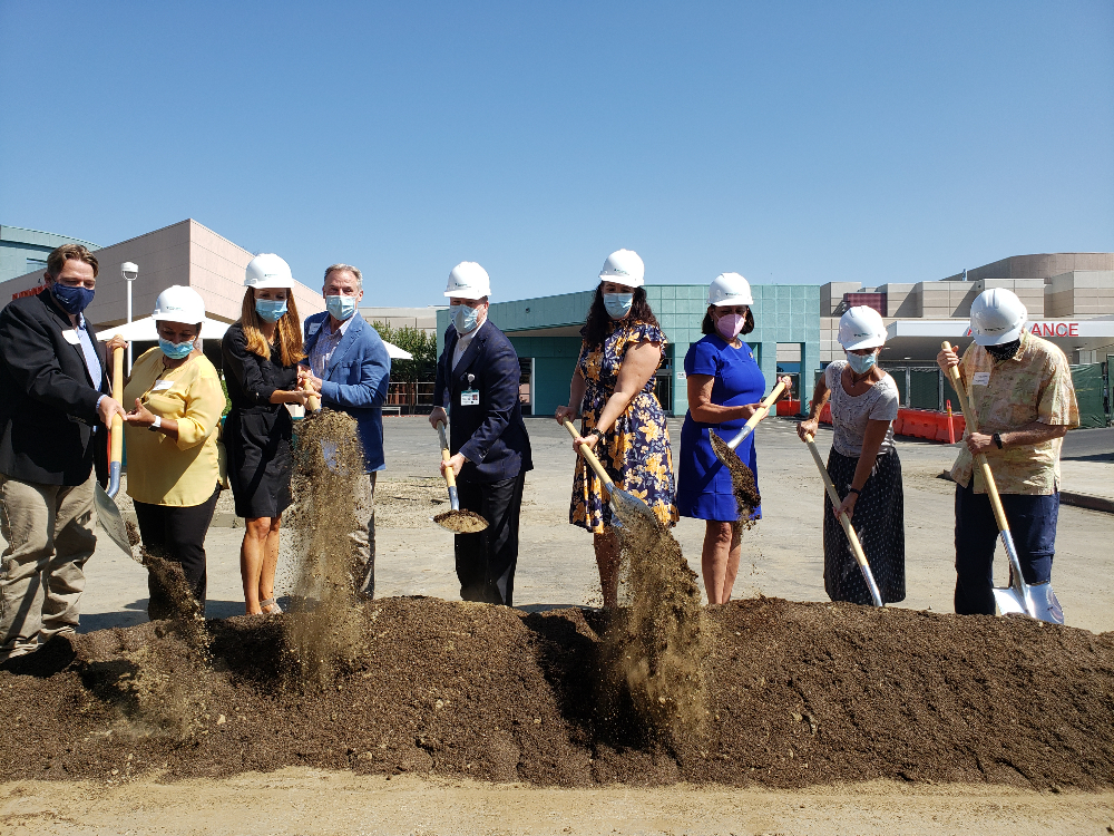 Various people with hardhats and shovels break ceremonial ground in hospital parking lot