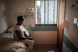 Black senior patient using mask looking through window at hospital